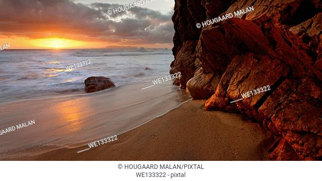 Landscape photo of dramatic sunset colours on a small beach cove. Kogelbay beach, Western Cape, South Africa