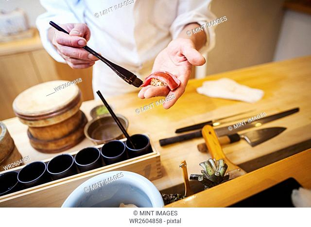 A chef working in a small commercial kitchen, an itamae or master chef making sushi, pasting sauce on fish