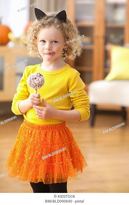 Caucasian girl in cat Halloween costume holding candy apple