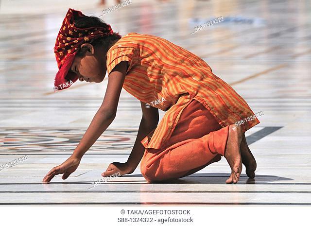 Little girl praying for the God in Golden Temple, Punjab Amritsar India