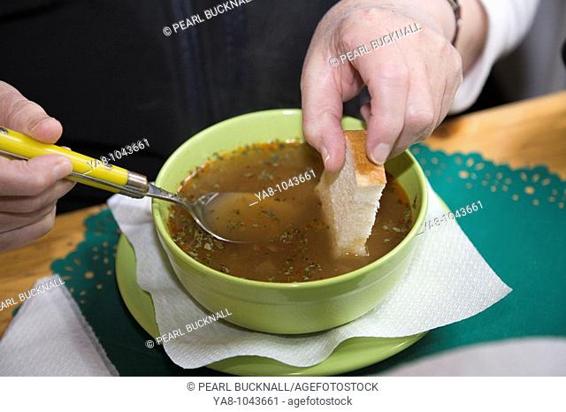 Bowl of brown soup on a table with woman dipping piece of white bread MR 08/16