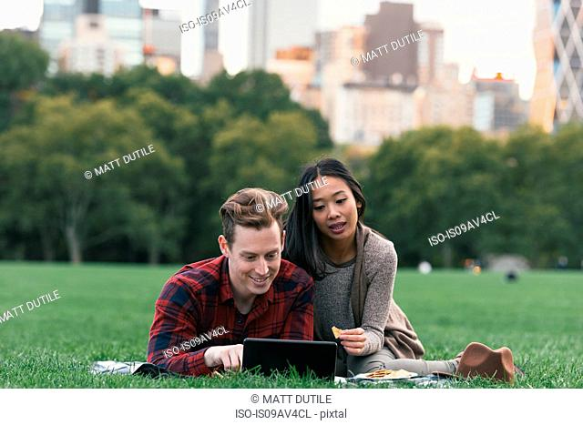 Mid adult couple on picnic blanket reading digital tablet in Central Park, New York, USA