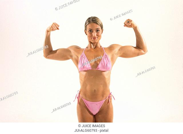 Female bodybuilder flexing biceps, portrait