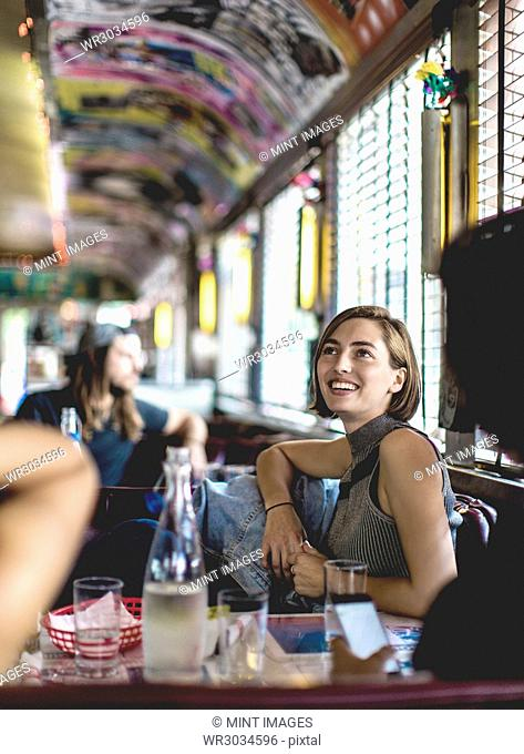 Smiling woman sitting in a booth in a diner looking up and talking to friends
