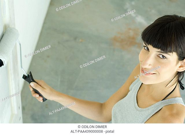 Woman painting with paint roller, high angle view