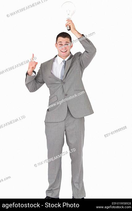 Portrait of a businessman holding a bulb above his head while pointing at someth