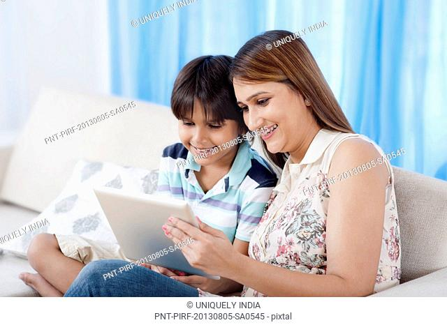Woman and her son using a digital tablet and smiling