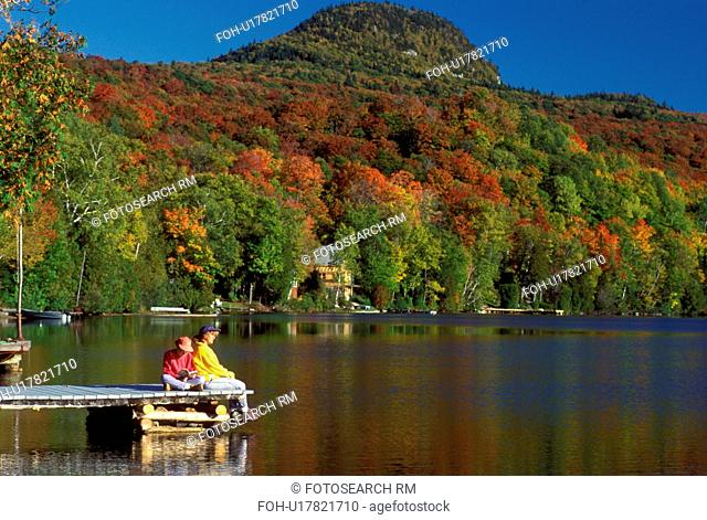Vermont, On a sunny fall day mother and daughter sit peacefully together relaxing on a dock reflecting in Long Pond of Westmore