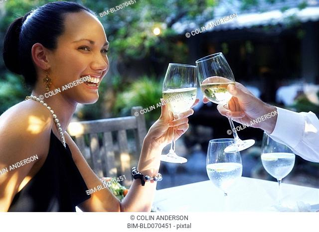 Pacific Islander woman toasting at restaurant
