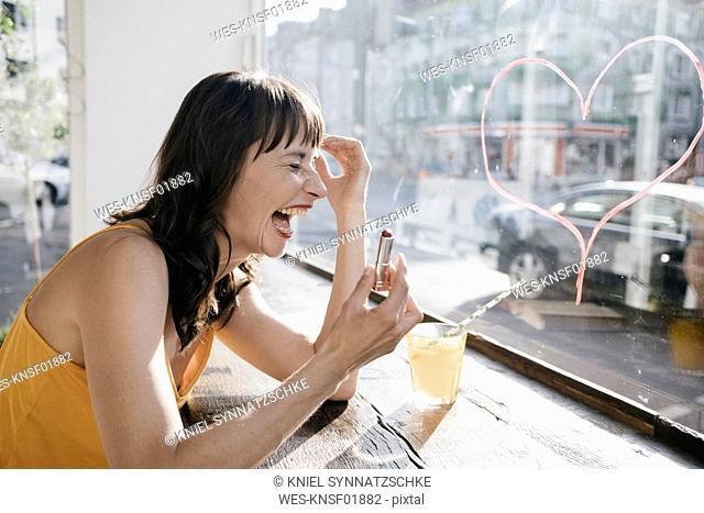Woman sitting in cafe drawing heart shape on window pane with lipstick
