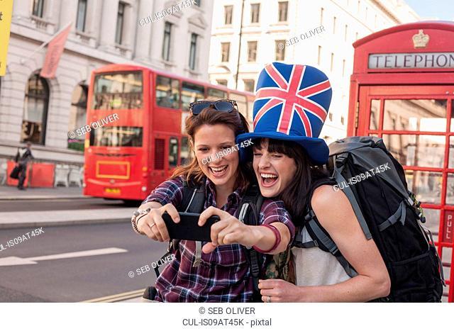 Two women backpackers wearing union jack hat taking smartphone selfie, London, UK