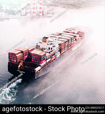 Barge loaded with containers heads to a port in the Atlantic Ocean, Canada