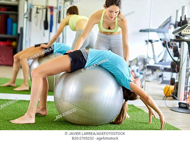Woman training with fitness ball, personal trainer