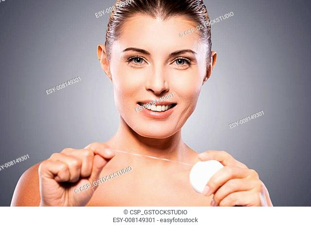 Woman with dental floss. Beautiful mature woman holding dental floss and smiling at camera while standing against grey background