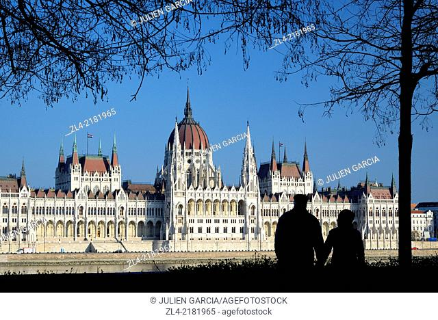 Silhouette of a couple of people and a tree in front of the Hungarian Parliament Building, a large neo-gothic monument built in the early 20th century