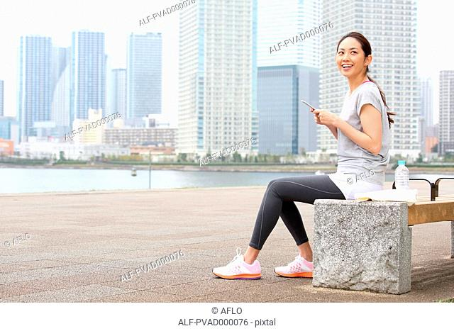 Attractive Japanese woman relaxing after training by a river downtown Tokyo, Japan