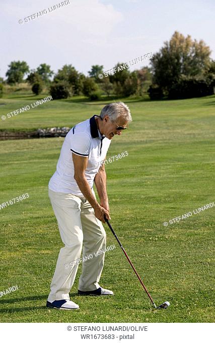 Mature man playing golf