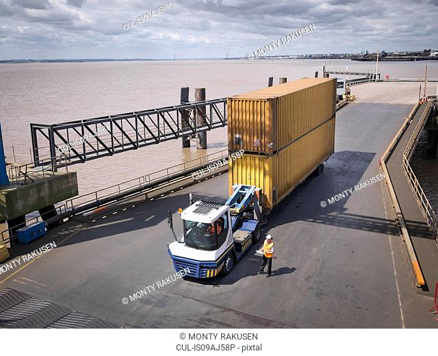 Elevated view of truck and shipping container on ramp to ship