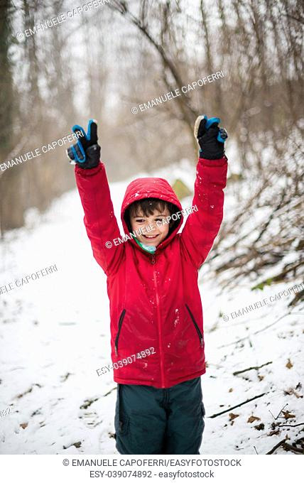 portrait of smiling child and arms raised to the sky with red hat in the snowy forest