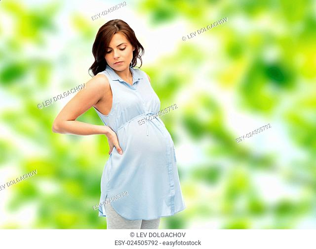 pregnancy, health, people and expectation concept - pregnant woman touching her back and suffering from backache over green natural background