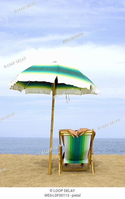 Woman lying in a deckchair at the beach