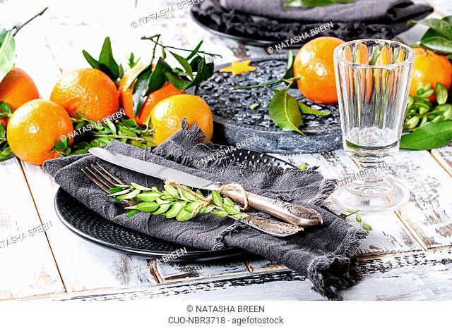 Christmas table decorations with clementines or tangerines with leaves and green branches on black ornate board. Empty glass and plate with cutlery and textile...
