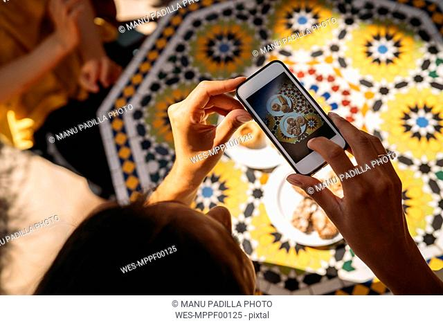 Close-up of woman taking a picture of cakes in a Moroccan cafe