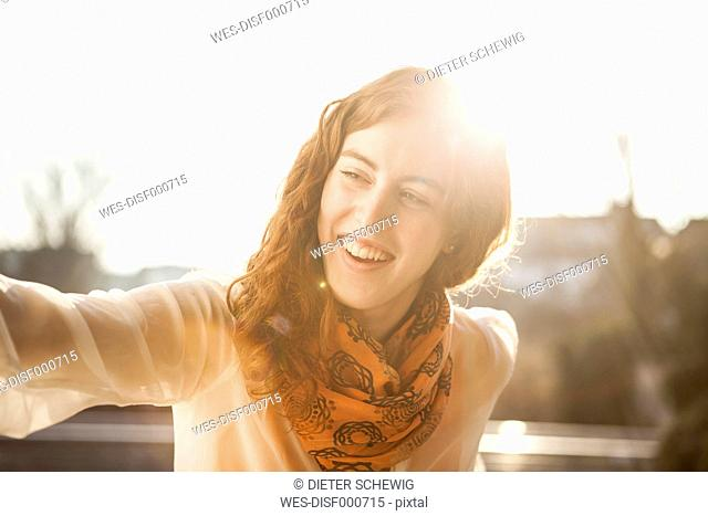 Portrait of smiling young woman standing in backlight