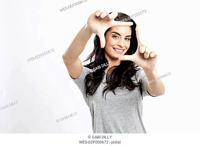 Portrait of smiling young woman building frame with her fingers