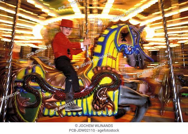 Jerez de la Frontera, a girl in tio pepe costume in a merry go round at Feria del caballo