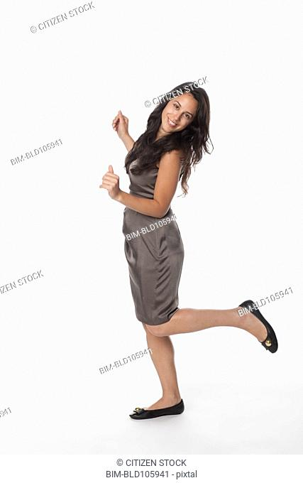 Smiling mixed race woman standing on one leg