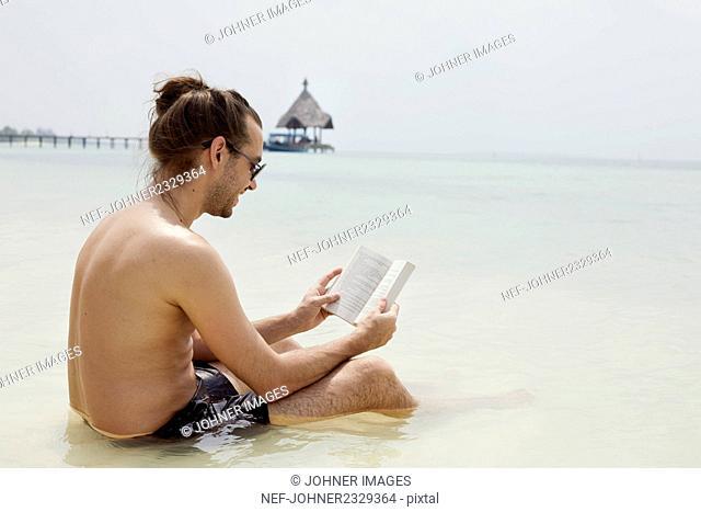 Man on beach reading book