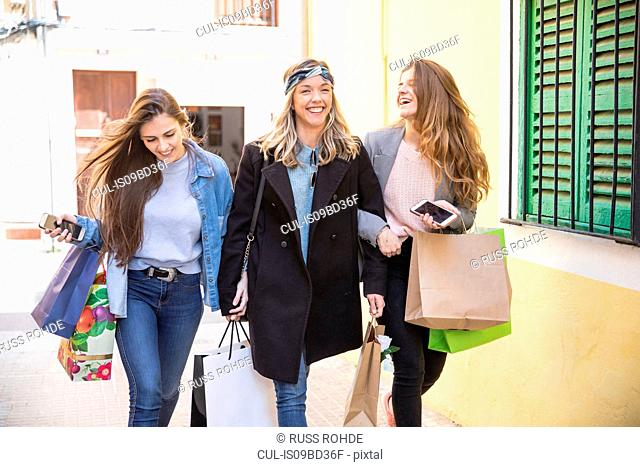 Friends out shopping and laughing in street