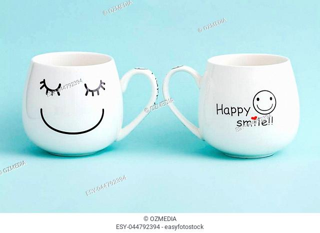 Smiling white coffee mugs on green background