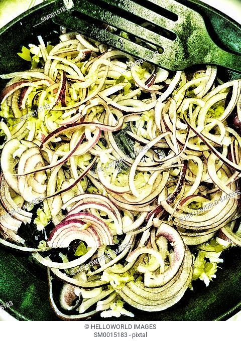 Red onions frying sautéing in frying pan