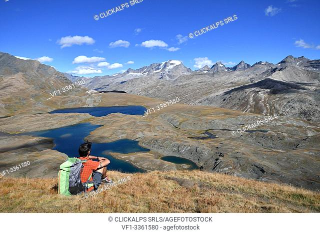 Trekker with Leita' and Rosset lakes and Gran Paradiso on background, Aosta Valley, Italy