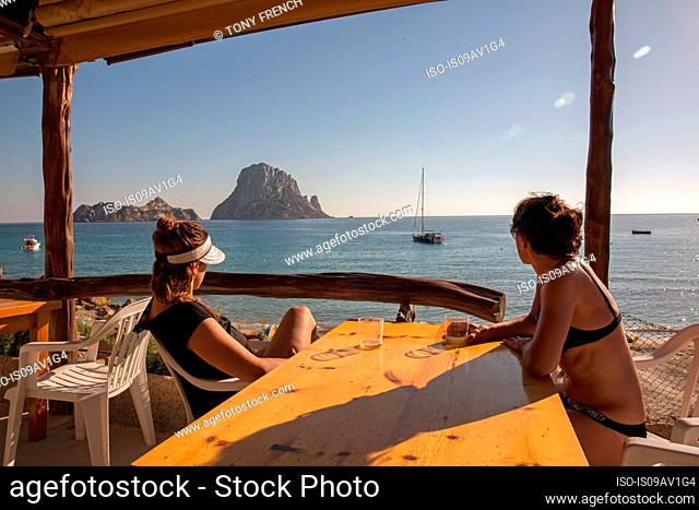 Two female tourists looking over to Es Vedra, Ibiza, Spain