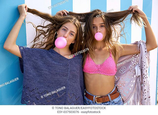Best friends teen girls group bubble gum in a summer blue stripes background