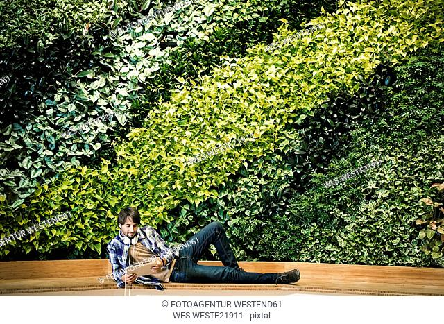 Young man sitting infront of green plant wall, using digital tablet