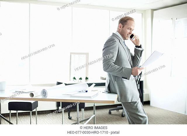 architect reviewing report while talking on the phone