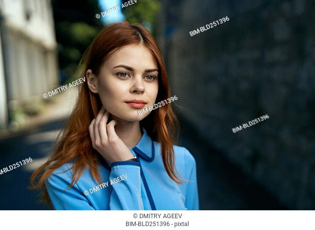 Pensive Caucasian woman near stone wall