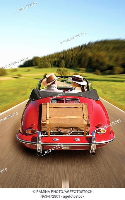 Middle aged couple on tour in a vintage Porsche in the , Black Forest, Germany