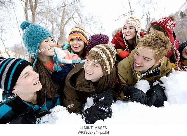 A group of friends, young boys and girls, lying in the snow