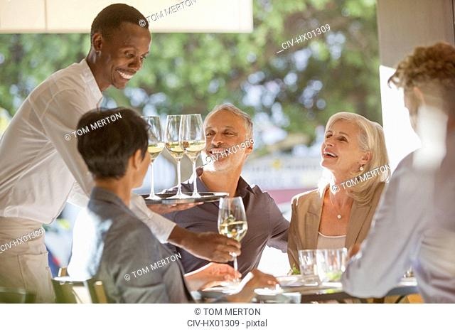 Waiter serving white wine to couples at restaurant table