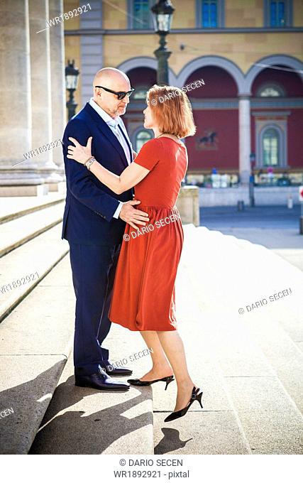 Senior couple embraces on staircase outdoors, Munich, Bavaria, Germany