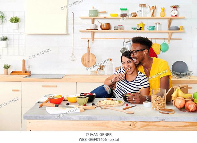 Multiethnic couple breakfasting together in the kitchen