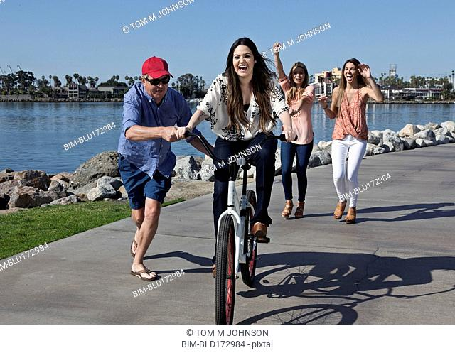 Man pushing woman on bicycle at waterfront