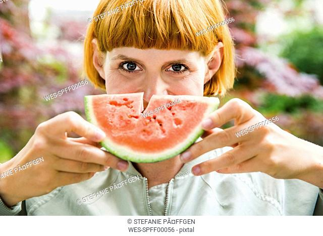 Portrait of redheaded woman holding slice of watermelon