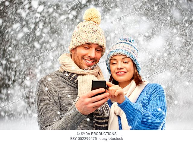 happy couple in winter clothes with smartphone