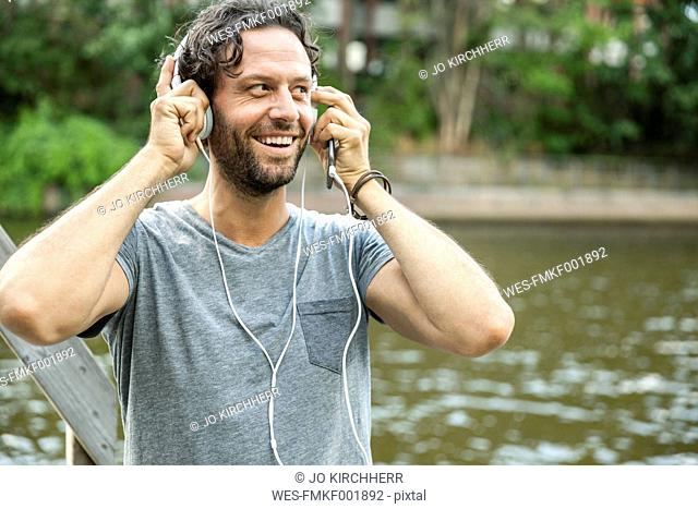 Happy man listening to music at the waterside